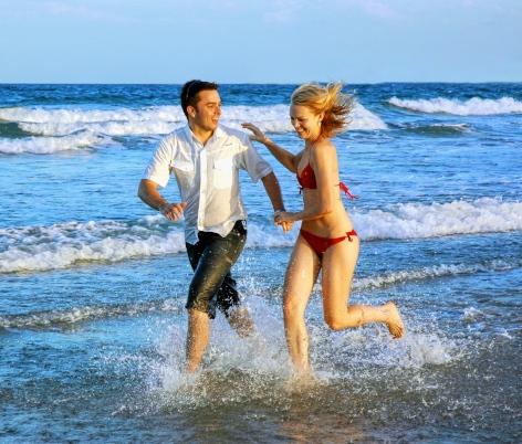 Giovani felici che corrono sul mare di Bibione